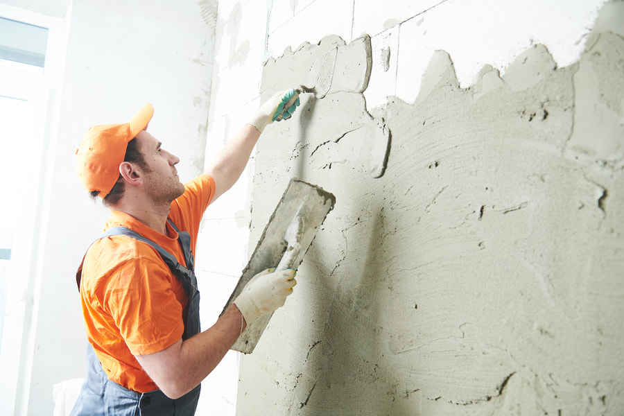 man smoothening the wall by putting cement